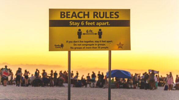 Social Distancing Sign on Florida Beach with crowd in background not complying in 2020 © Joel Hartz