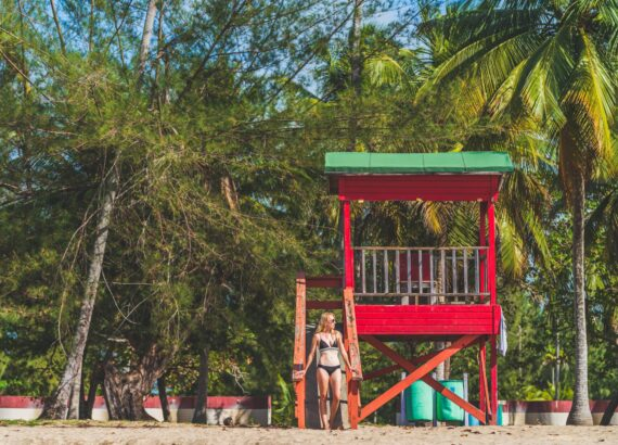 Woman and Red lifeguard hut Luquillo, Puerto Rico